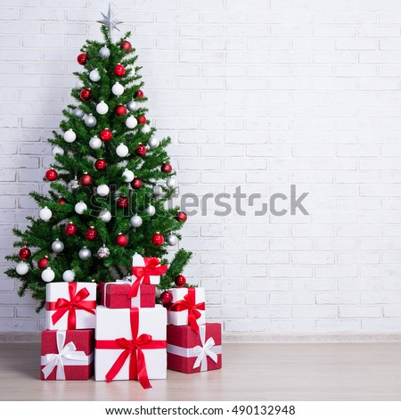 christmas tree with colorful balls and gift boxes over white brick wall #490132948