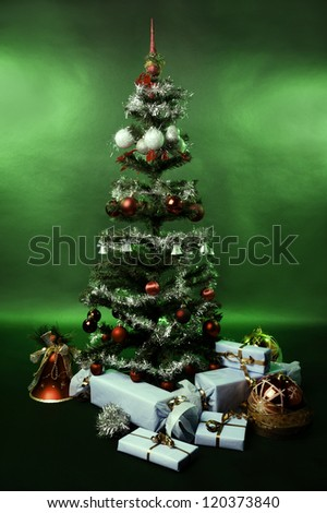 Christmas tree with decoration and gifts on a green background