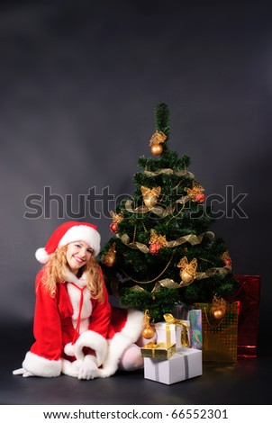 christmas tree with different gifts on black and santa girl