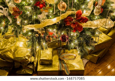 Christmas tree with gold wrapped gifts and presents and lights reflecting off the paper and ribbons under the tree/