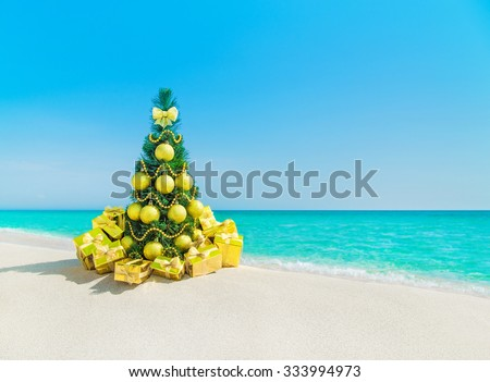 Christmas tree with golden decorations and packed gift boxes at tropical ocean beach. New Years vacation in hot countries background concept