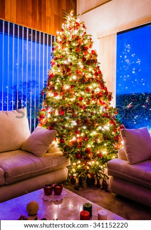 Christmas tree with golden lights in a cozy living room with windows at the evening
