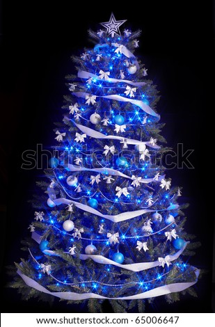 Christmas tree with light and blue star. Black background.