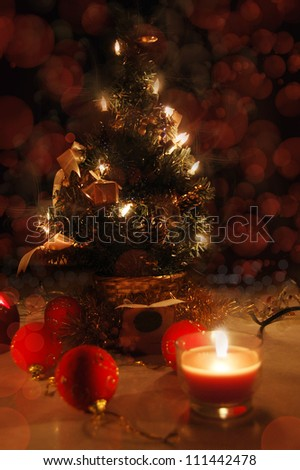 Christmas tree with lights and candles over black, tree in focus
