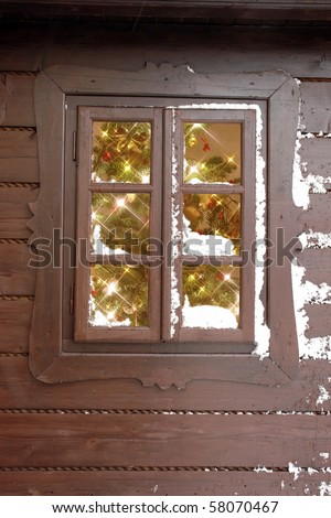 Christmas tree with lights seen through a wooden cabin window - stock photo