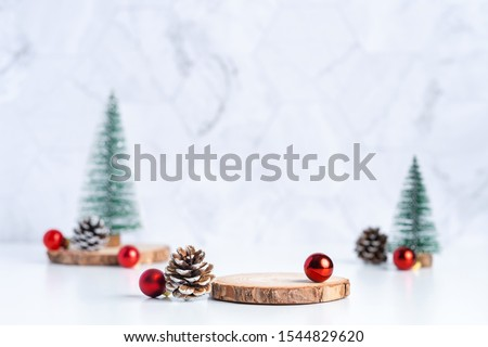 christmas tree with pine cone and decor xmas ball and empty wood log plate on white table and marble tile wall background.clean minimal simple style.holiday still life mockup to display design