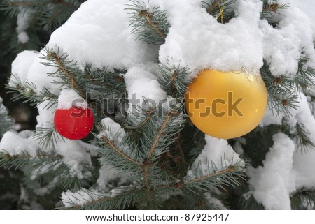 Christmas tree with red and yellow balls and snow on it