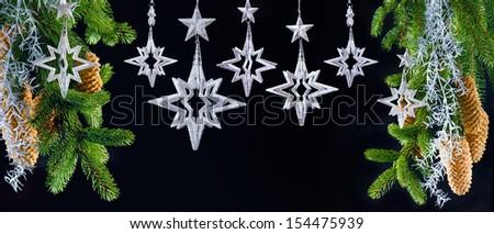 christmas tree with shiny silver stars over black. festive christmas decoration. seasonal holidays background