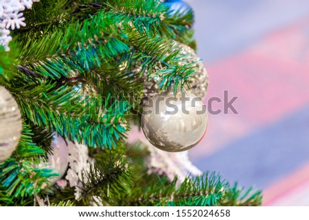 Christmas tree with silver bauble ornaments. Decorated Christmas tree closeup. Balls and illuminated garland with flashlights. New Year baubles macro photo with bokeh. Winter holiday light decoration #1552024658
