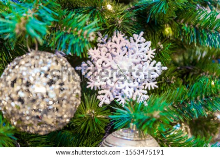 Christmas tree with silver bauble ornaments. Decorated Christmas tree closeup. Balls and illuminated garland with flashlights. New Year baubles macro photo with bokeh. Winter holiday light decoration #1553475191