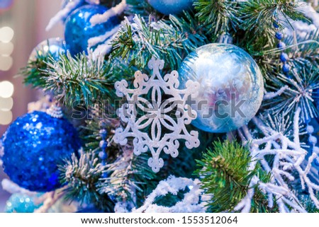 Christmas tree with silver bauble ornaments. Decorated Christmas tree closeup. Balls and illuminated garland with flashlights. New Year baubles macro photo with bokeh. Winter holiday light decoration #1553512064