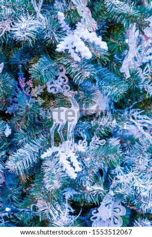 Christmas tree with silver bauble ornaments. Decorated Christmas tree closeup. Balls and illuminated garland with flashlights. New Year baubles macro photo with bokeh. Winter holiday light decoration #1553512067