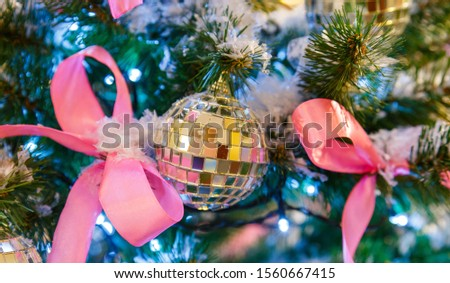 Christmas tree with silver bauble ornaments. Decorated Christmas tree closeup. Balls and illuminated garland with flashlights. New Year baubles macro photo with bokeh. Winter holiday light decoration #1560667415