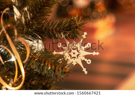 Christmas tree with silver bauble ornaments. Decorated Christmas tree closeup. Balls and illuminated garland with flashlights. New Year baubles macro photo with bokeh. Winter holiday light decoration #1560667421