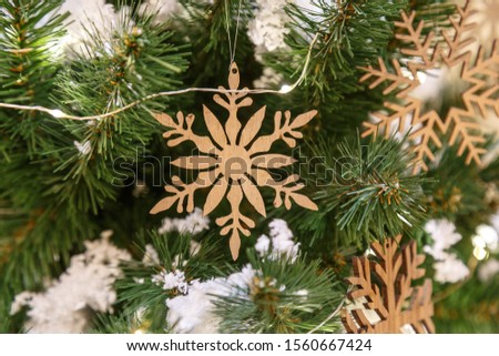 Christmas tree with silver bauble ornaments. Decorated Christmas tree closeup. Balls and illuminated garland with flashlights. New Year baubles macro photo with bokeh. Winter holiday light decoration #1560667424