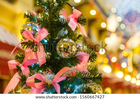 Christmas tree with silver bauble ornaments. Decorated Christmas tree closeup. Balls and illuminated garland with flashlights. New Year baubles macro photo with bokeh. Winter holiday light decoration #1560667427