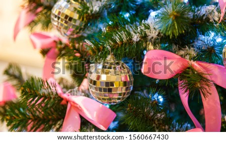 Christmas tree with silver bauble ornaments. Decorated Christmas tree closeup. Balls and illuminated garland with flashlights. New Year baubles macro photo with bokeh. Winter holiday light decoration #1560667430