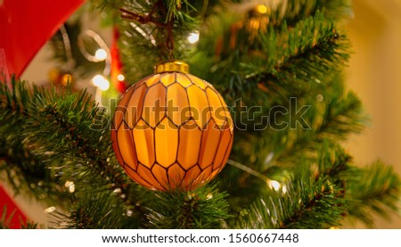 Christmas tree with silver bauble ornaments. Decorated Christmas tree closeup. Balls and illuminated garland with flashlights. New Year baubles macro photo with bokeh. Winter holiday light decoration #1560667448