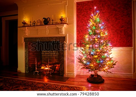 Christmas tree with vintage multicolor lights in an old fashioned traditional interior with brick fireplace and warm burning fire log in hearth