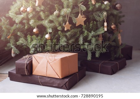 Christmas tree with wooden rustic decorations and presents under it in loft interior. #728890195