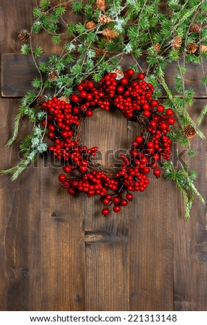 Christmas tree wreath from red berries over rustic wooden background