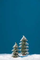 Christmas trees stand in the snow on a blue background.