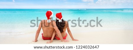 Christmas tropical sun vacation destination vacation holidays santa hat couple relaxing sitting on beach banner background for text advertisement for New Year holiday season. Blue ocean copy space. #1224032647