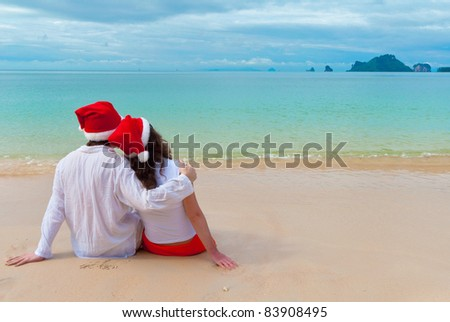 Christmas tropical vacation. Romantic couple in santa hats sitting on beach