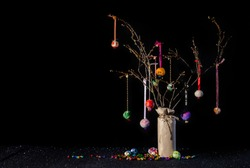 Christmas twig tree table decoration in rustic theme with colourful handmade baubles. Black background and glittery base with jungle bells and copy space.