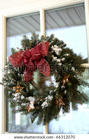 Christmas twig wreath with snow on house door