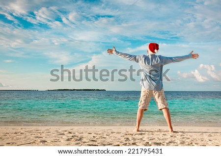 Christmas vacation - man in santa hat on the tropical beach