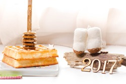 Christmas waffle with honey on ceramic plate . Decorated by small wool boots on the wood wis wooden numbers of the year 2017. Served with napkin and honey spoon