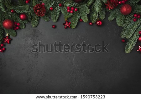 Christmas winter arch with fir branches, red balls on natural black background. Xmas greeting card. Holiday time. Happy New Year. Space for text. View from above, flat lay.