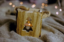 Christmas winter background. Wooden decorative lantern in the form of a cube with a carved herringbone on the bedspread close-up, the concept of a cozy christmas, home warmth, hygge atmosphere