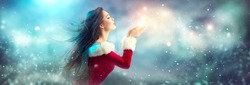 Christmas Winter Fashion Girl blowing  Magic snow in Her Hand. Fairy. Beautiful New Year and Xmas Tree. Holiday Hairstyle, Makeup. Gift. Beauty Model woman on Holiday Blurred blue Background, sale