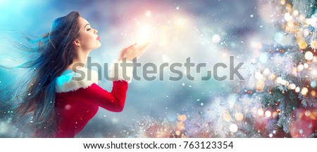 Christmas Winter Fashion Girl blowing  Magic snow in Her Hand. Fairy. Beautiful New Year and Xmas Tree. Holiday Hairstyle, Makeup. Gift. Beauty Model woman on Holiday Blurred blue Background, sale #763123354