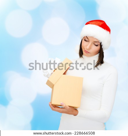 christmas, winter, happiness, holidays and people concept - woman in santa helper hat with gift box over blue lights background