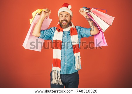 9608231a99ce6 Christmas winter holidays celebration. Hipster hold shopping bags on red  background. New year