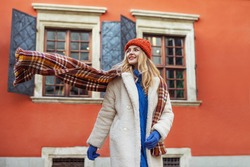 Christmas, winter holidays, lifestyle conception: happy smiling woman wearing white faux fur coat, colorful scarf, hat, walking in street of European city. Copy, empty space for text
