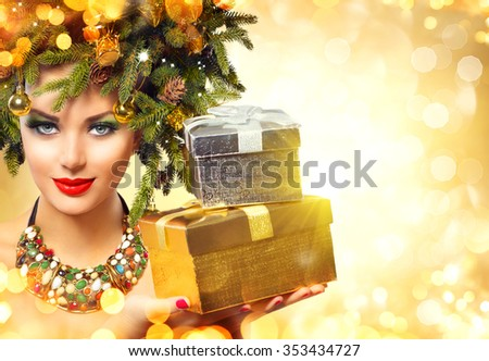Christmas Winter Woman with Christmas Gifts. Fairy. Beautiful New Year and Christmas Tree Holiday Hairstyle and Make up. Beauty Fashion Model Girl With Present Box over golden glowing background