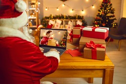 Christmas wish is sure to come true. Over shoulder Santa Claus sitting at desk, looking at laptop computer screen spying on little child who's writing and sending letter in which he asks for a present