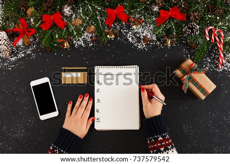Christmas wish list writing. Woman creating present list for winter holidays. Top view, preparing for xmas and new year concept #737579542
