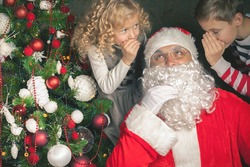 Christmas Wish 2016! Santa Claus and Little Kids Telling Wishes in Santa Claus's Ear. Cristmas Scene near Christmas Tree
