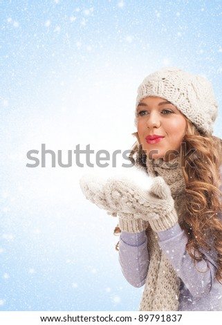Christmas woman blowing snow, against blue background