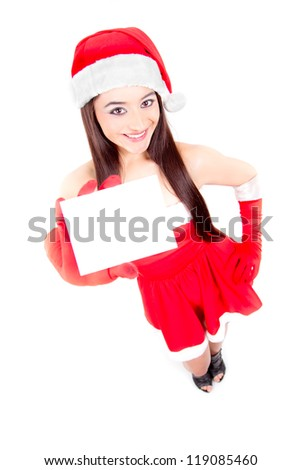 Christmas woman holding empty paper card standing in Santa costume