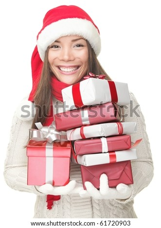 Christmas woman holding gifts wearing Santa hat. Smiling woman portrait of a beautiful mixed Asian / Caucasian model. Isolated on white background. - stock photo
