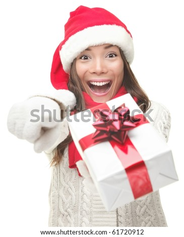 Christmas woman holding / giving gift excited pointing. Happy smiling woman in santa hat giving you a present being joyful, fresh and cheerful. Asian / Caucasian model isolated on white background.