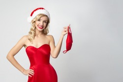 Christmas woman in red dress  and santa hat   removes the  medical mask   on white backhround with  copy sppace  . christmas sale  and  advertising concept.