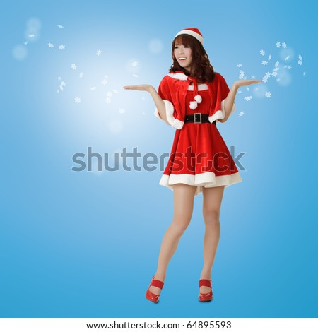 Christmas woman showing happy and surprised expression in dream with snowflakes over blue background.
