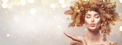 Christmas Woman with golden spruce tree wreath hairstyle on blurred pastel background. Beautiful Xmas model girl presenting hand, showing product, kiss. Hair style decorated, baubles. Christmas wishes